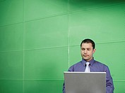 Businessman with laptop in green office (thumbnail)