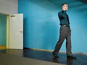 Businessman on mobile phone in blue office (thumbnail)