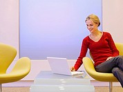 Woman sitting in a chair looking at laptop