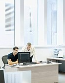 Two businessmen in an office looking at a computer