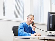 Businessman on a telephone at his computer in an office