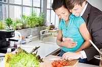 Couple embracing in a kitchen chopping cherry tomatoes