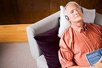 Man wearing headphones sleeping on sofa with book