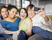 Four friends on a sofa taking a picture of themselves