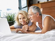 Couple looking at laptop in bed