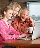 Couple with girl on laptop in modern home