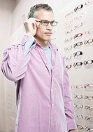 Man trying on glasses in optical shop (thumbnail)