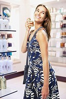 Woman spraying perfume on herself in store