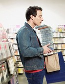 Man carrying stack of CDs in store