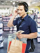 Man wearing headphones with shopping bags in store