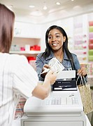 Woman paying for items at a cashier in store (thumbnail)