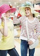 Two girls trying on hats in store