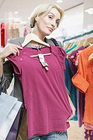 Woman holding shirt up to herself in store