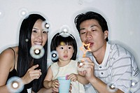 Couple with young girl blowing bubbles
