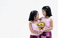 Two young girls holding flowers