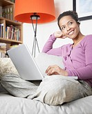 Woman wearing headset with laptop on sofa