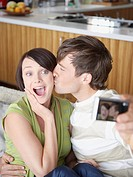Couple taking picture of themselves kissing