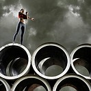 Woman stretching on top of large cylinders