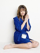 Woman in blue bathrobe using