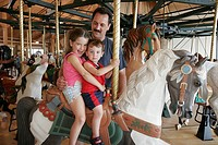 Davis Mercantile Building, carousel, boy, girl, father, ride. Shipshewana. Indiana. USA.