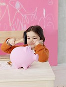 Girl with hammer and piggy bank