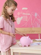 Blonde girl with money and piggy bank