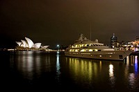 Australia, Sydney, A night scene looking across Sydney Harbor to the iconic Opera House, large yacht in foreground