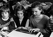 Group of junior age girls using microcomputer