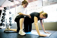 Pregnant woman doing pilates exercises  Personal trainer positioning a pregnent woman on the floor during a pilates session in a gymnasium  Pilates is...