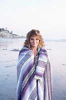 Mature woman wrapped in blanket on beach, portrait