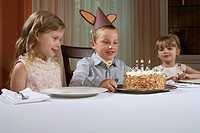 Three children 4-6 sitting at table, looking at birthday cake