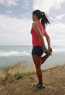 Young woman exercising by sea, side view