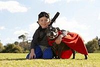 Boy 6-7 wearing costume, sitting with dog in park surface level, portrait
