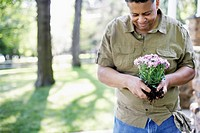 Mature man planting flowers outdoors, smiling, upper half