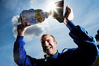 Racecar Driver Holding Trophy