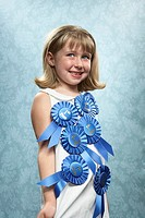 Girl 6-7 with 1st place ribbons on chest, smiling, close-up