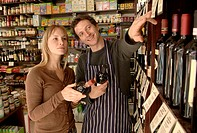 Male shop assistant helping female customer choose wine