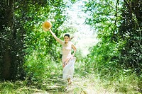 Young woman in sundress running along wooded path, holding up sun hat