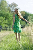 Young woman in sundress standing in field, rear view
