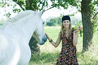 Young woman petting horse, holding apples in hand
