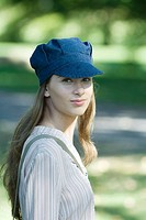 Young woman in park, wearing cap, portrait (thumbnail)