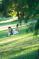 Young woman lying on grass, smiling at camera