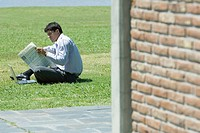 Businessman sitting on ground with laptop, reading newspaper