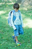 Boy walking across grass wearing backpack
