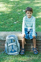Boy sitting on low wall, backpack by side, looking at camera