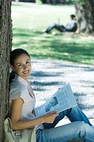 Woman sitting on ground with newspaper in park, leaning against tree, smiling at camera