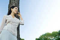 Woman using cell phone, leaning against tree, low angle view