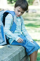 Boy sitting on low wall wearing backpack, playing with rocks
