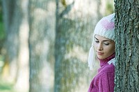 Young woman wearing knit hat, leaning against tree, looking over shoulder