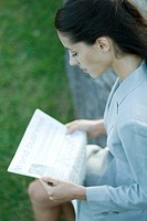 Businesswoman sitting on bench, reading newspaper